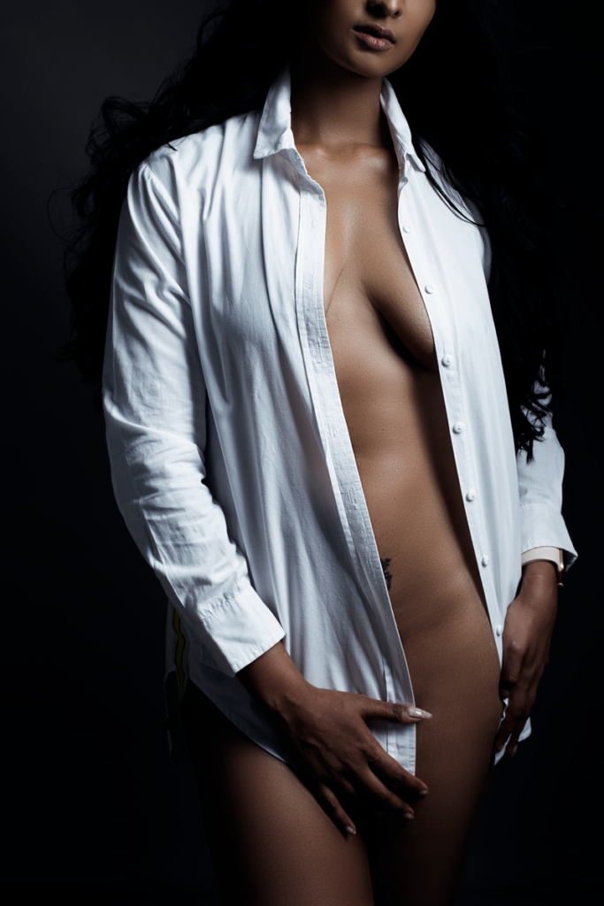 Stunningly feminine boudoir shot with woman with white shirt taken in studio by Loci Photography