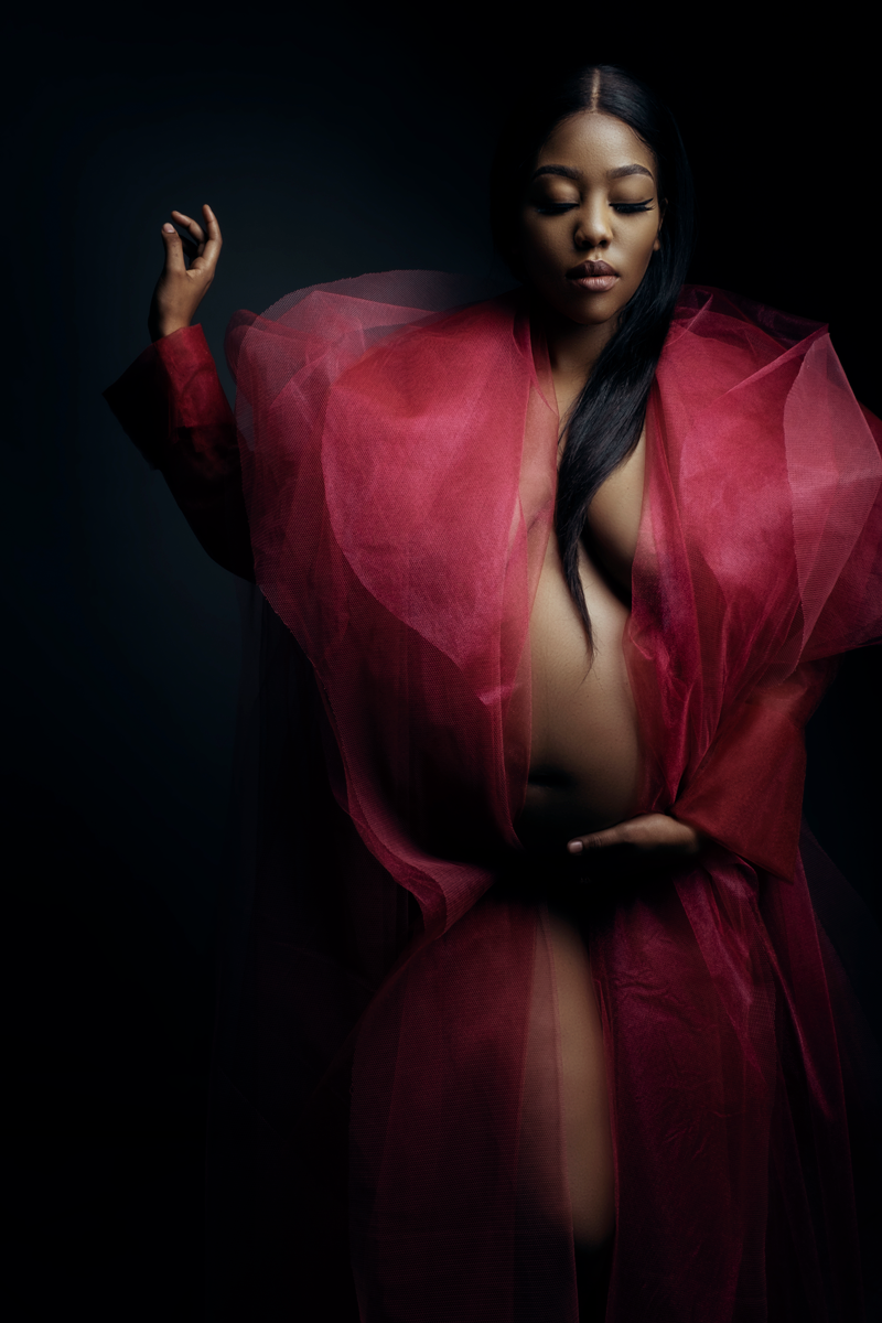 The red Nicolassi coat being used in a special way, during a maternity shoot with Loci Photography showing off the clothing range exclusive to Loci Photography
